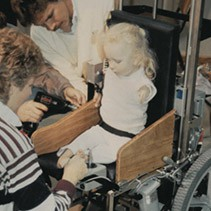 Young client being fitted for a new wheelchair in the 1980s.
