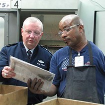 Center Industries employee Gavin Williams shows Major General Randall Fullhart his part in the production line.