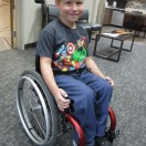Wheelchair and Posture Seating Clinic Client in his red wheelchair.