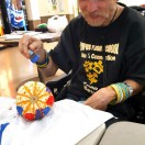 Timbers resident working on a marbled pumpkin craft.