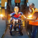 Client smiling while being loaded on to school bus in wheelchair.