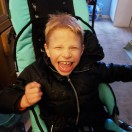 Young Equipment Fund Client smiling at the camera while in his adaptive stroller.