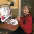 Equipment Fund Client smiling and giving a thumbs up towards the camera as she uses her DaVinci Pro Magnifier.
