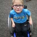 Little boy smiling at camera in his blue manual wheelchair.