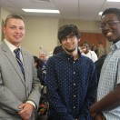 Three male SACT Youth Program students stand smiling at the camera.