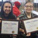 Two female SACT Youth Program graduates smiling at camera while holding their certificates.