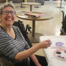 Timbers resident smiling at camera while working on a painting activity.