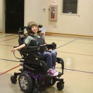Young girl in powerchair smiling at camera.