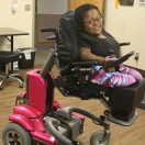 Wheelchair Clinic client in her pink adjustable powerchair smiling at camera.