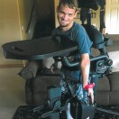 Equipment Fund client in smiling while using his stander.