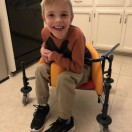 Young Equipment Fund client smiling at the camera while sitting in his pre-gait trainer.