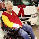Equipment Fund is sitting in her power wheelchair smiling in front of her new white wheelchair van with a big red bow on the hood.