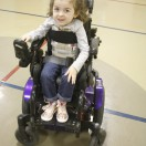 Little girl smiling at camera in purple powerchair.