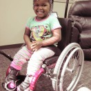 Little girl smiling at camera, seated in pink manual wheelchair.
