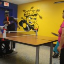 Clients playing ping pong in the activity room of Adult Day Services.