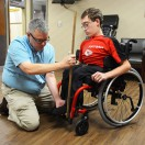 Client in red wheelchair getting an evaluation.