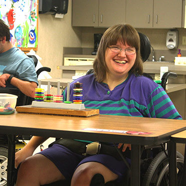 Female Adult Day Services client smiling at camera while sitting at a table with an activity.