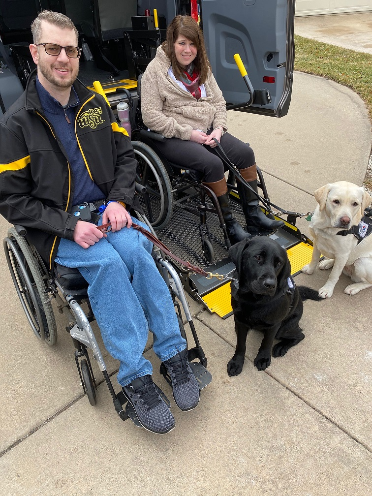 Equipment Fund clients sitting outside of accessible van with their service dogs.