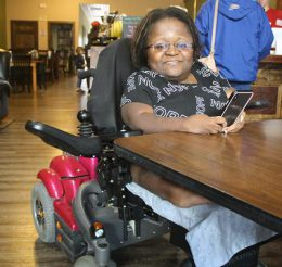 Client is smiling at camera in pink powerchair at a cafe.