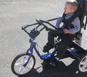Child riding his adaptive tricycle purchased and customized with assistance from the CPRF Equipment Fund.