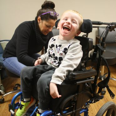 CPRF occupational therapist working with a young boy's wheelchair, who is laughing towards the camera.