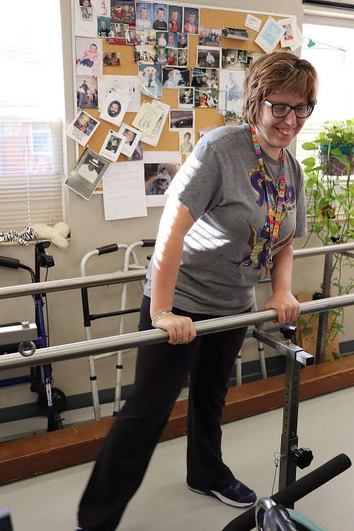 Exercise & Wellness client smiling while using parallel bars.