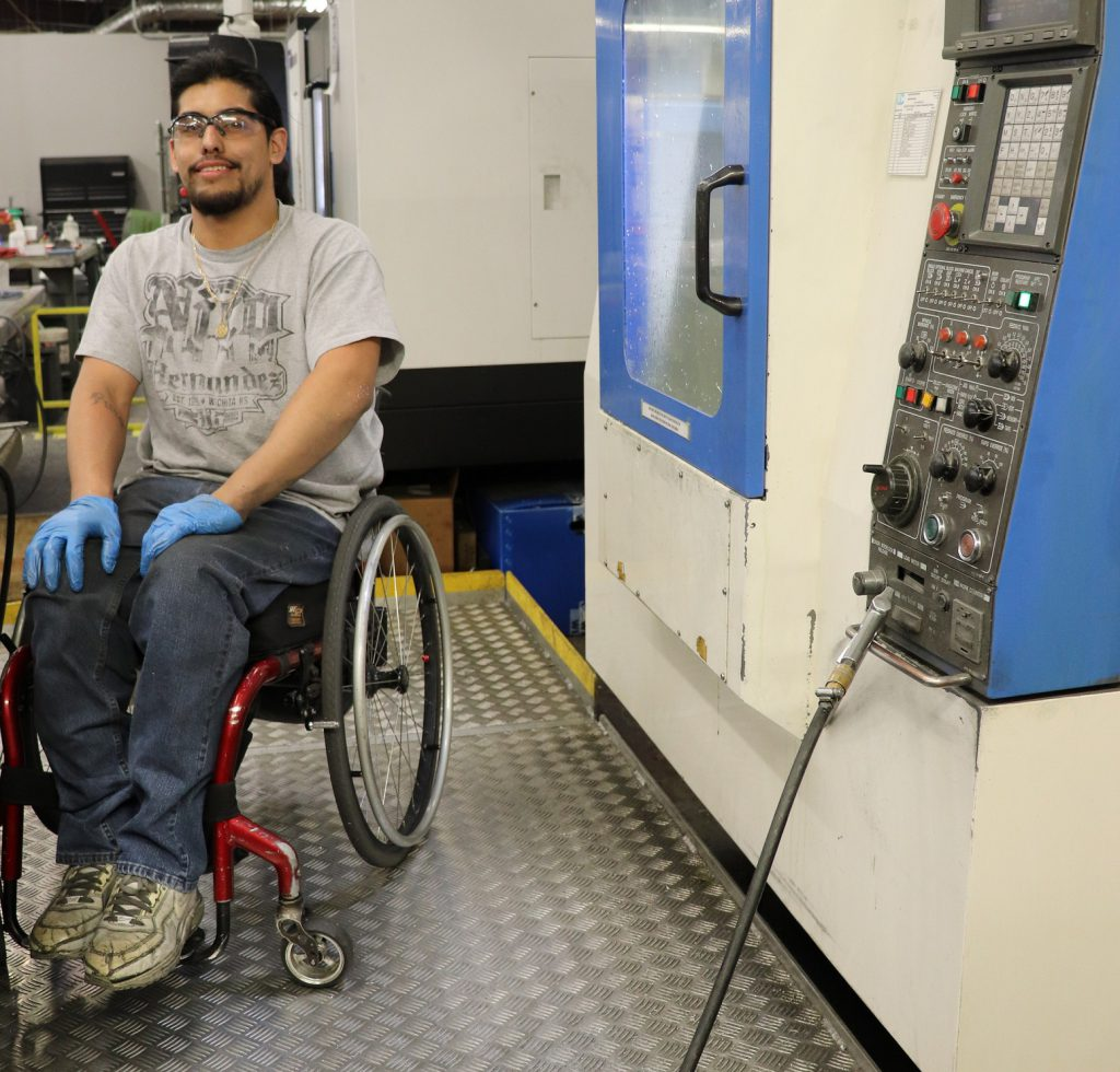 Job Placement client looking at camera at modified CNC workstation