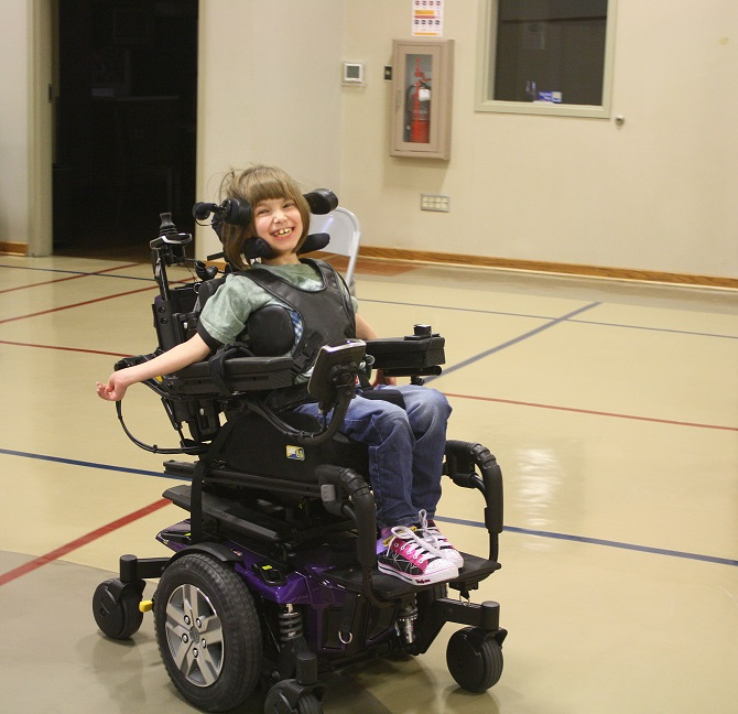 Wheelchair & Posture Seating Clinic client test driving her seating system that is powered by a head array control system.