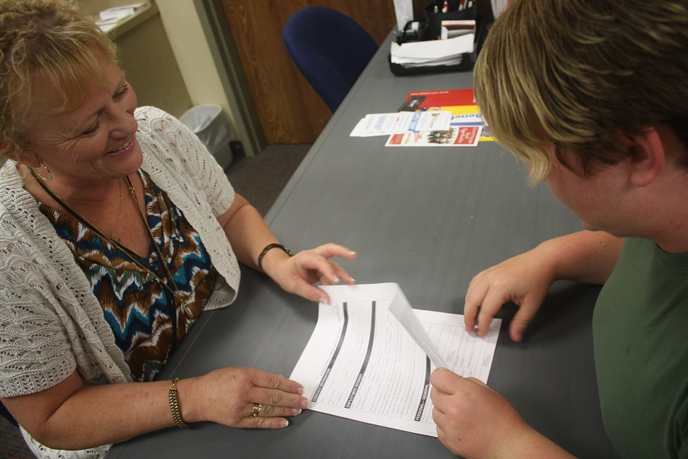 CPRF Director of Job Placement helping a client with paperwork.