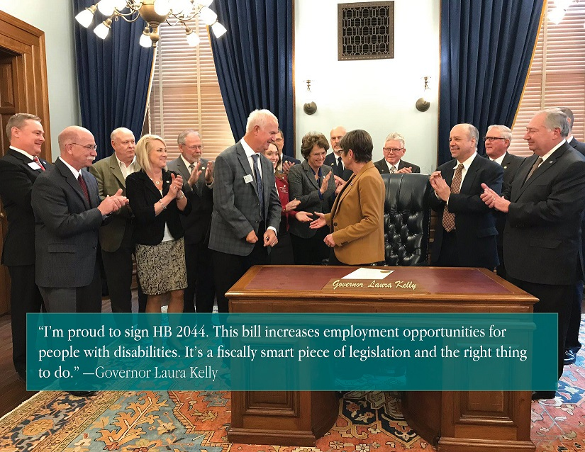 Governor Laura Kelly celebrating with group signing HB 2044 into law.