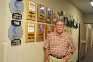 Dave Jones stands in front of United Way award wall