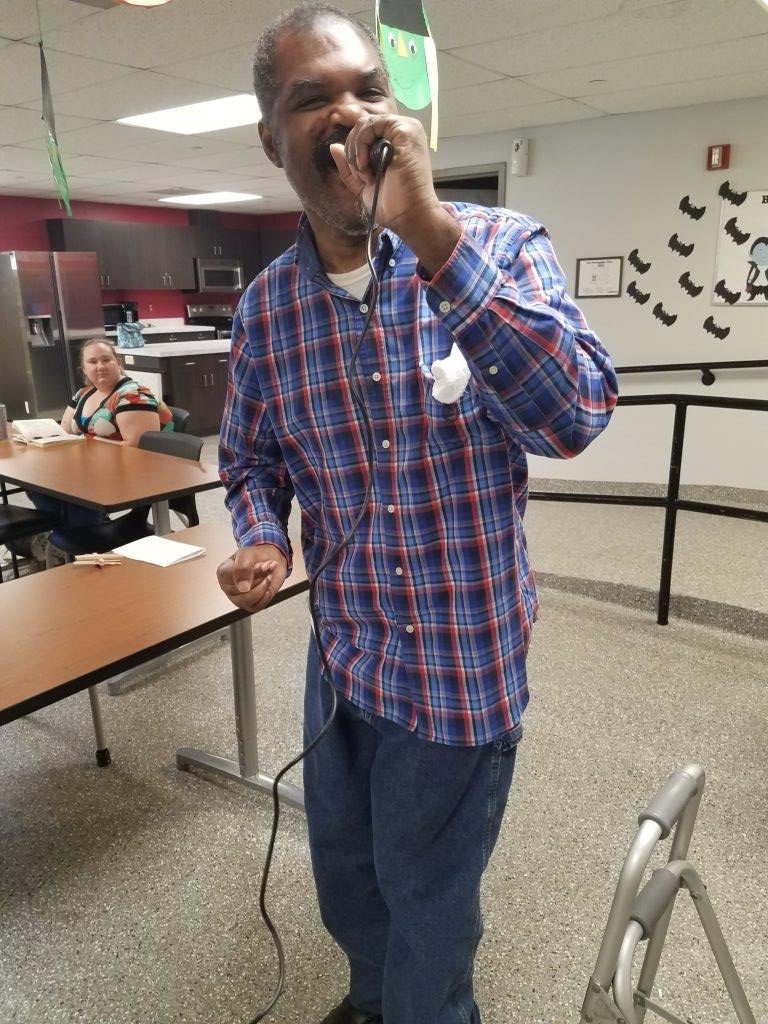 Adult Day client singing karaoke,.