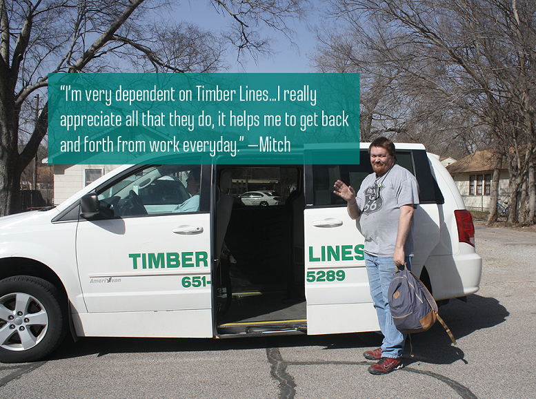 Timber Lines client is smiling and waving outside of accessible van.